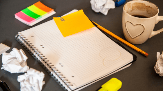 A desk that is holding a grid notebook, a bunch of rolled up paper balls, a dirty coffee mug and a bunch of sticky notes. The image is the header for a blog post on how to overcome a creative block.