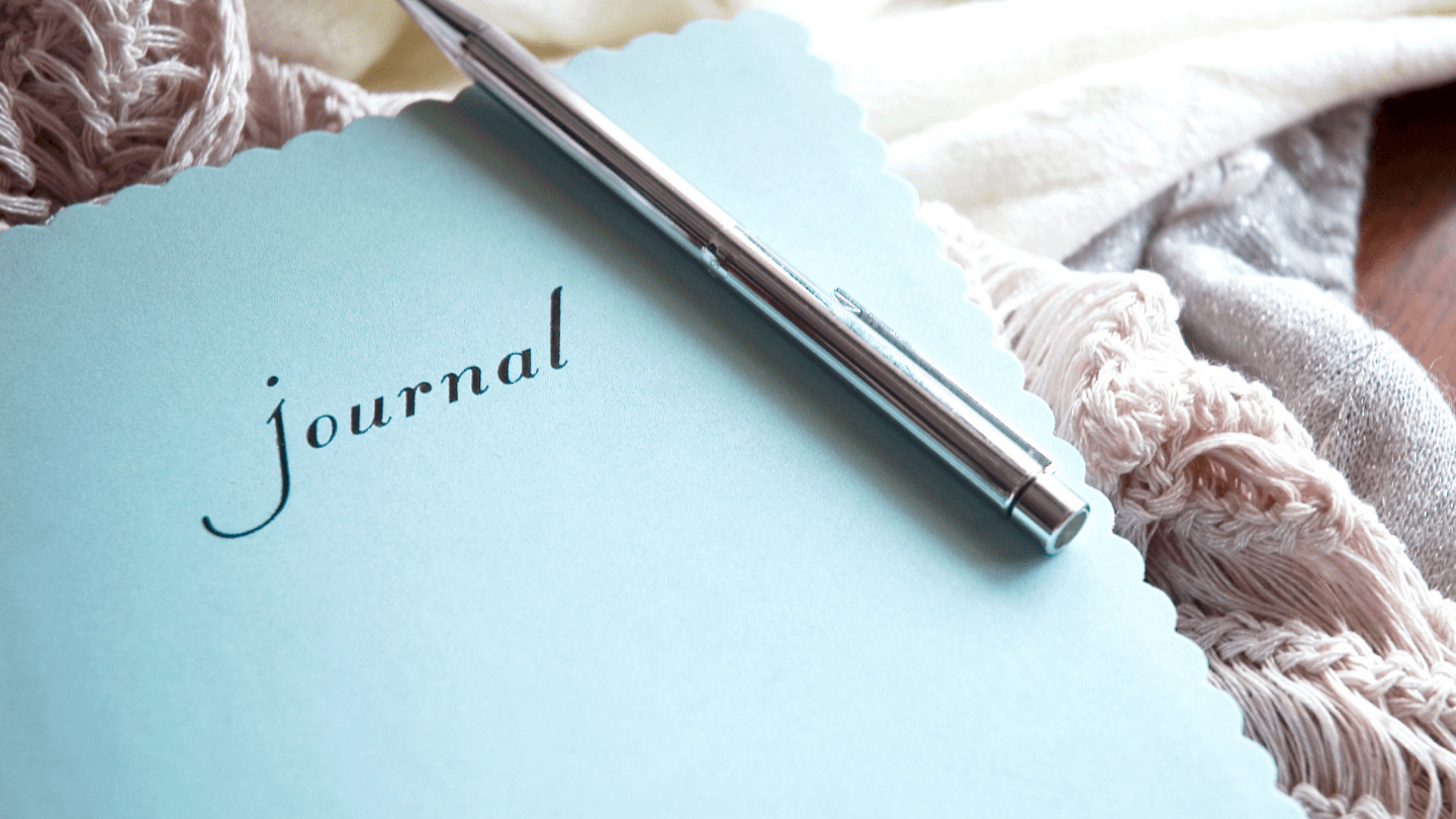 A blue journal and silver pen. The photo is for a blog post on journal prompts for mental health.